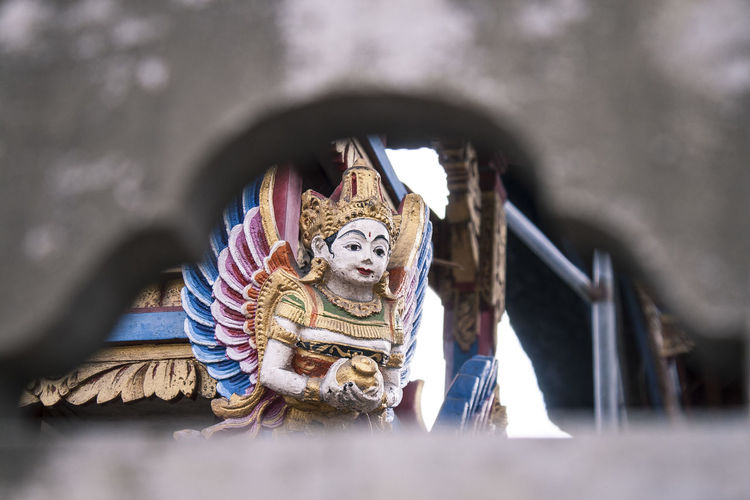 Looking through a temple wall Colors Hinduism INDONESIA Shrine Travel Architecture Art And Craft Belief Buddhism Building Built Structure Creativity Culture Day Explore Human Representation No People Religion Representation Sculpture Secret Selective Focus Spirituality Statue Temple
