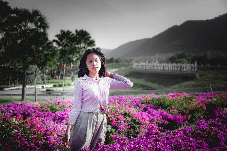Portrait of smiling young woman standing by purple flowering plants