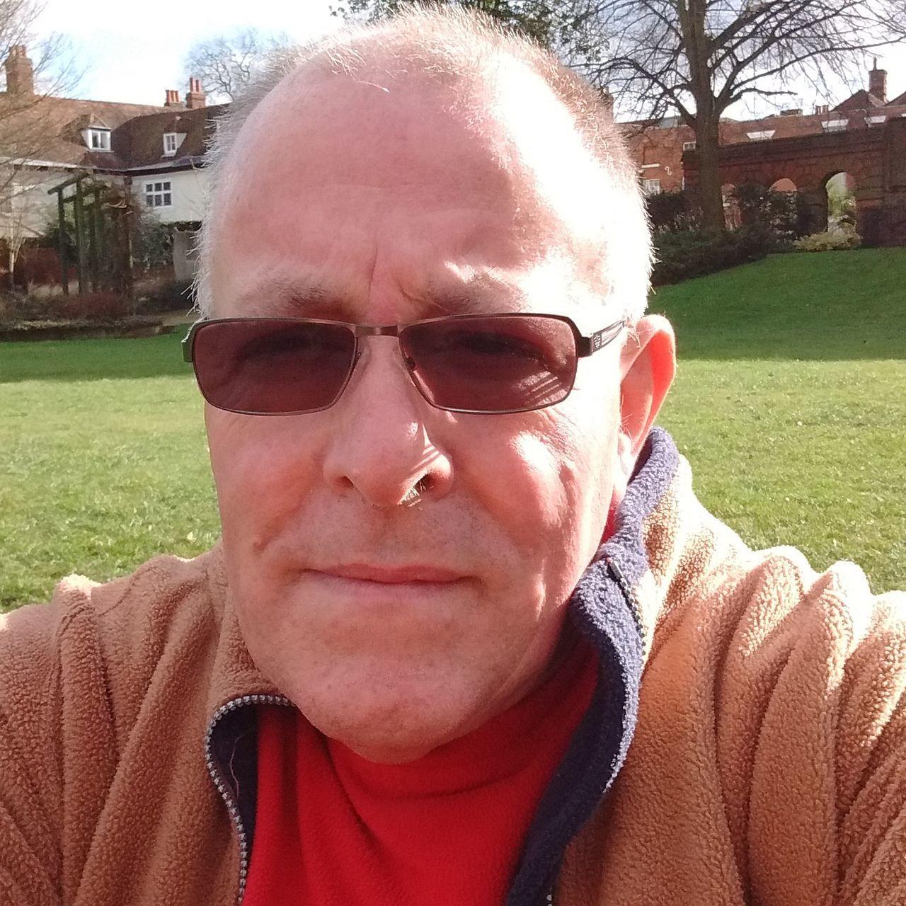 Close-Up Of Man Wearing Sunglass On Grassy Field