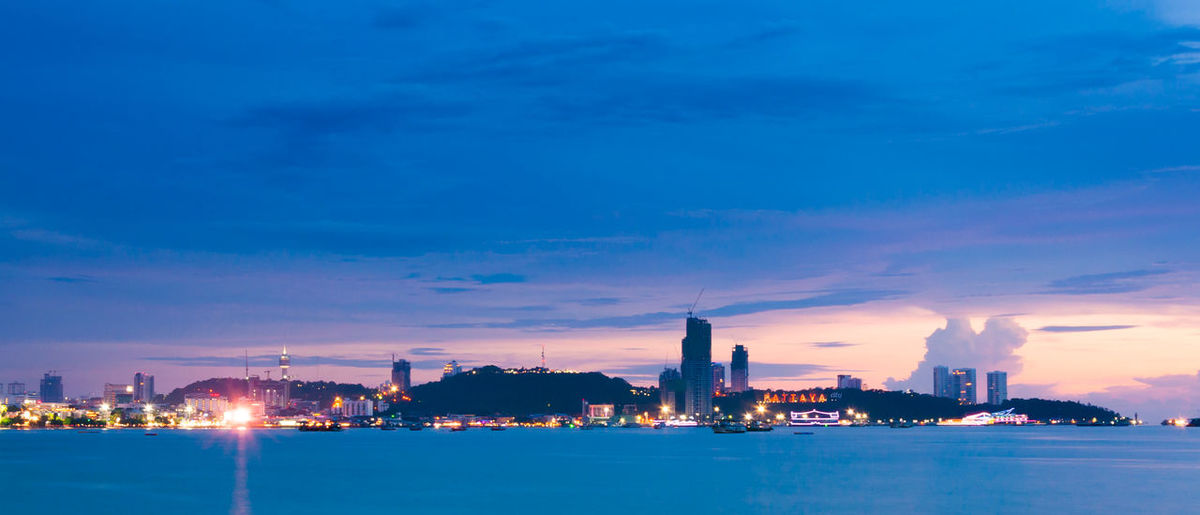Illuminated city by sea against sky during sunset