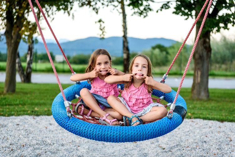 Portrait of twin sisters on swing at playground