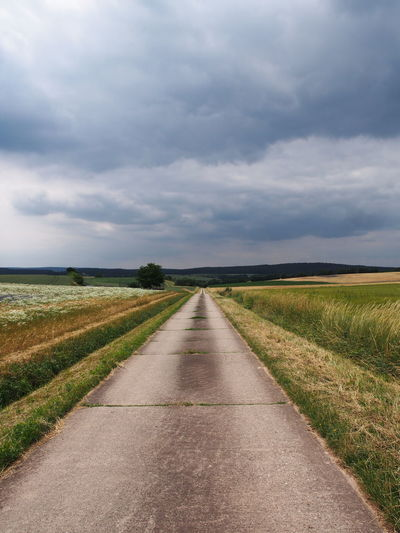 Cloud - Sky Day Diminishing Perspective Direction Environment Field Grass Land Landscape Nature No People Outdoors Plant Road Scenics - Nature Sky Straight The Way Forward Tranquil Scene Tranquility Transportation vanishing point