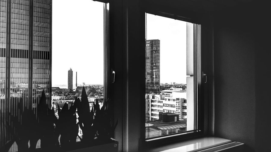 People in city buildings seen through glass window