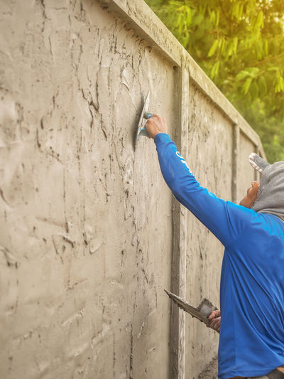 Side View Of Man Fixing Wall