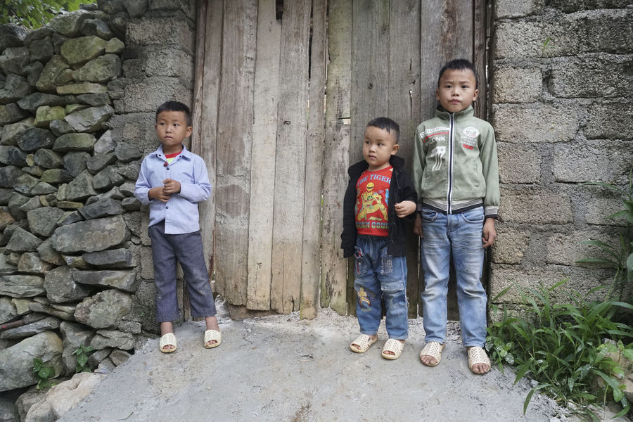 Faces of Hmong Tribe in Dong Van, Vietnam. Hmong Life Hmong Tribe Vietnam Vietnamese Childhood Boys Standing Full Length Group Of People Males  Men Child Portrait Looking At Camera Casual Clothing Front View Togetherness Day Offspring Emotion People Females Smiling Architecture Outdoors Innocence