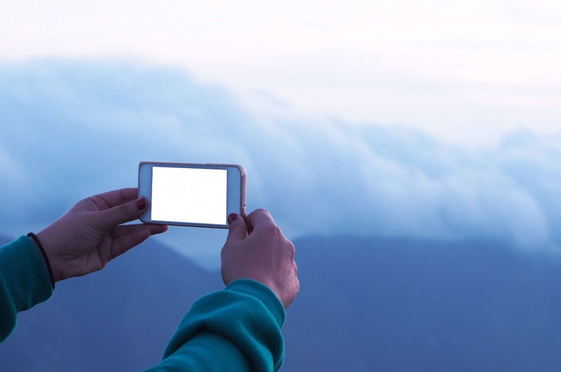 Cropped Image Of Woman Photographing Against Cloudy Sky