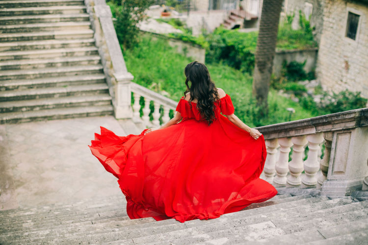 Rear View Of Woman In Red Dress Moving Down On Steps
