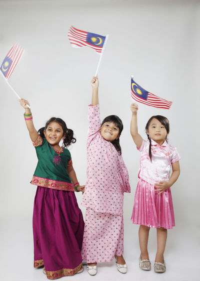 malaysia multi racial kid holding flag Celebration Happiness Indian National Day Patriotism Traditional Clothing Child Childhood Chinese Females Flag Front View Girls Harmony Innocence Malay Ethnicity Malaysia Malaysian Merdeka Multi Racial Smiling Standing Togetherness White Background Women