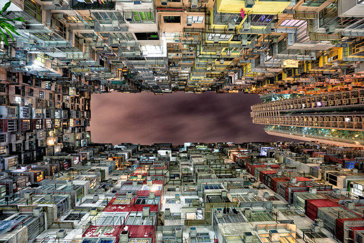 Directly below shot of buildings against sky in city
