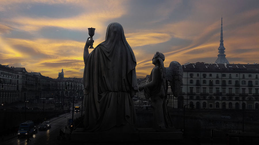 Sunset over the magical Turin. Silhouette of a statue of Faith with a Holy grail in hands and an angel near on a dramatic sky background (Church of Gran Madre) Church Of Gran Madre Holy Grail Sculpture Statue Mystic Mystic Turin Turin Turin Italy Piedmont Italy Piedmont Symbol Legents Mole Antonelliana Mole Antoneliana Night Sunset Sunset_collection Art And Craft Travel Angel Cityscape Hystory