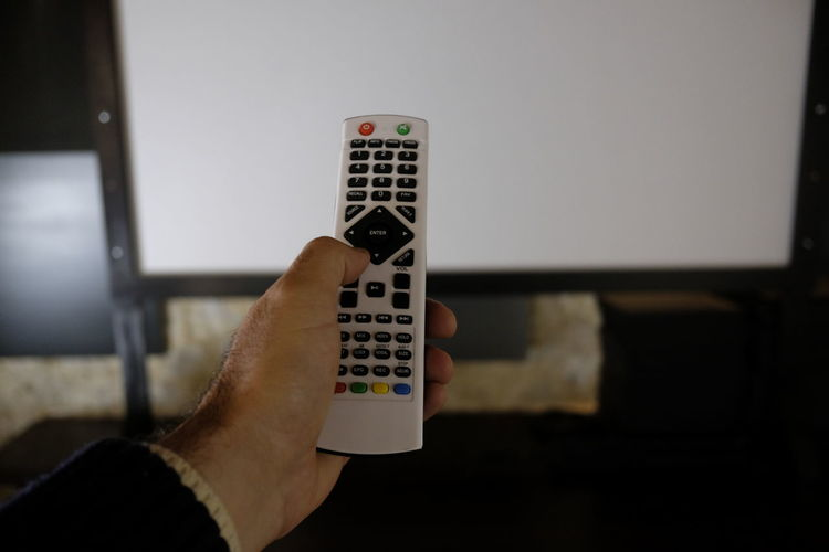 Cropped Hand Of Man Using Remote At Home