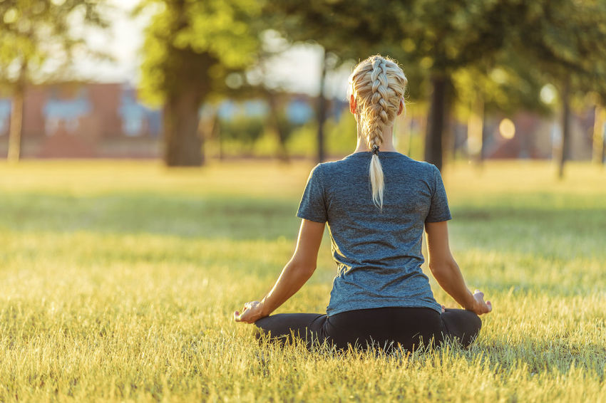 Blond Woman Doing Yoga In Grass Beautiful Meditation Sitting Woman barefoot Blond Braided Exercising Grass Lawn Leggings Leisure Activity Lifestyles Nature One Person Outdoors Park Plant Pose Pretty Relaxation Exercise Stretching Sunset Yoga Young Adult