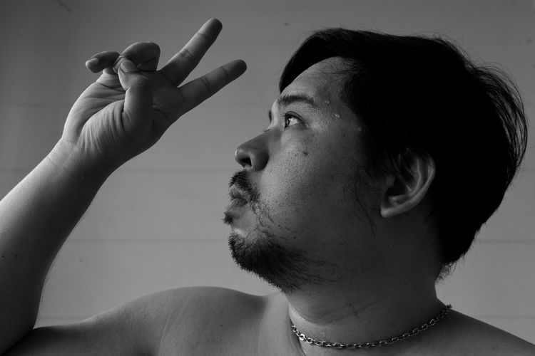 Close-up of serious man showing peace sign against wall