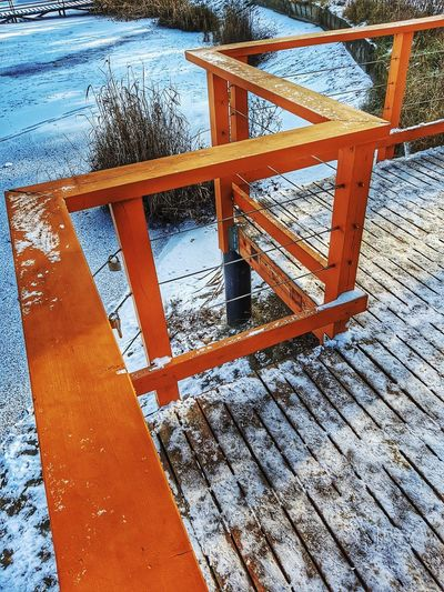 High angle view of snow covered footpath by railing during winter