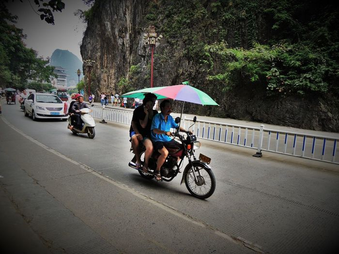 People riding bicycle on road in rain