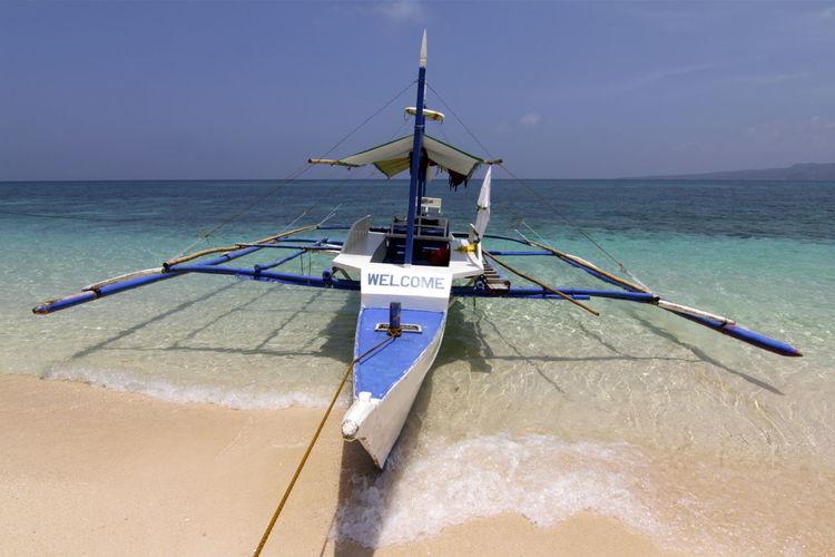 Catamaran on shore against clear sky
