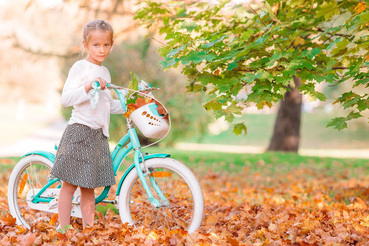 Portrait of smiling boy on bicycle during autumn