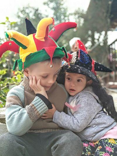Cute siblings wearing hats sitting outdoors