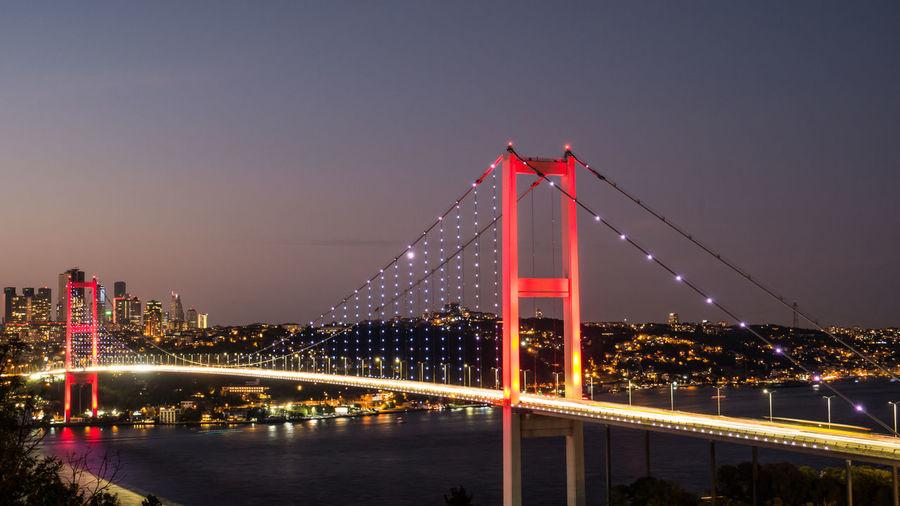 View of suspension bridge in city at night
