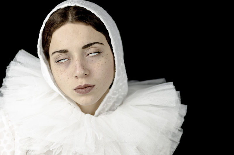 Close-up of woman wearing white costume against black background