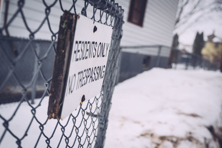 Close-up of sign on chainlink fence in snow