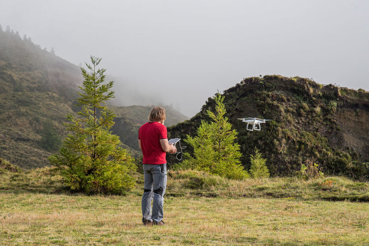 Rear view of man flying drone with remote control while standing on grass against sky