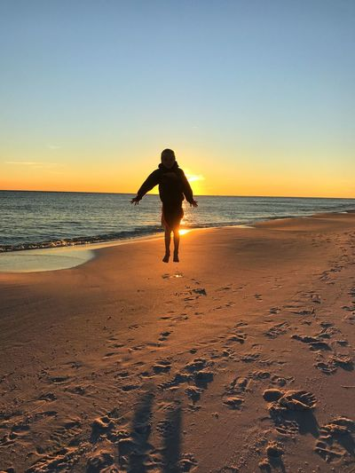 Full length of boy jumping on sand at beach against clear sky during sunset