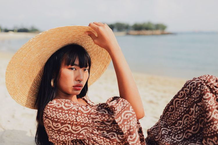 Portrait of young woman wearing hat sitting at beach