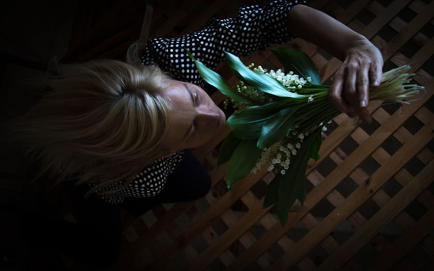 High Angle View Of Woman Smelling Flowers