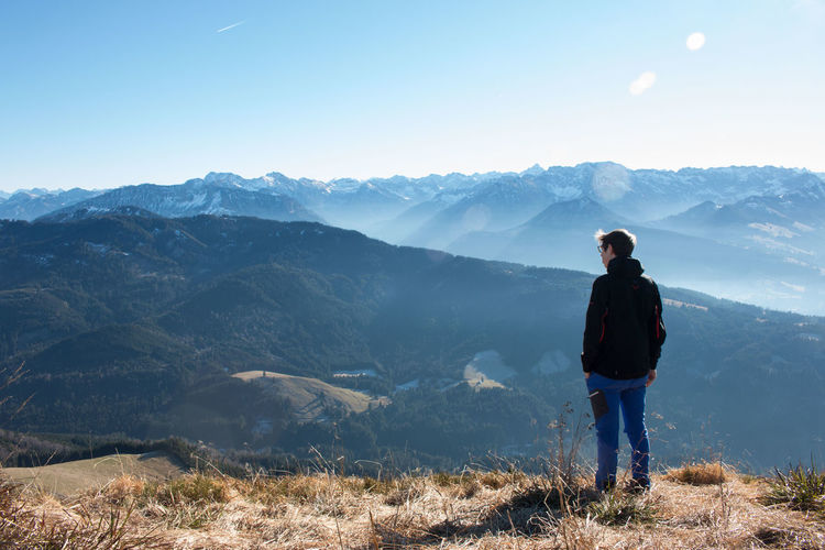 Man standing on peak while looking at mountains against sky