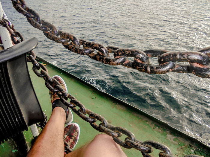 Low Section Of Man Sitting By Chains On Boat In Sea
