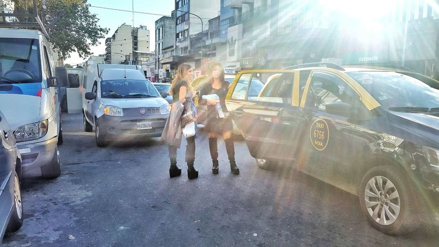 Women Standing Near Taxi Against Cloudy Sky