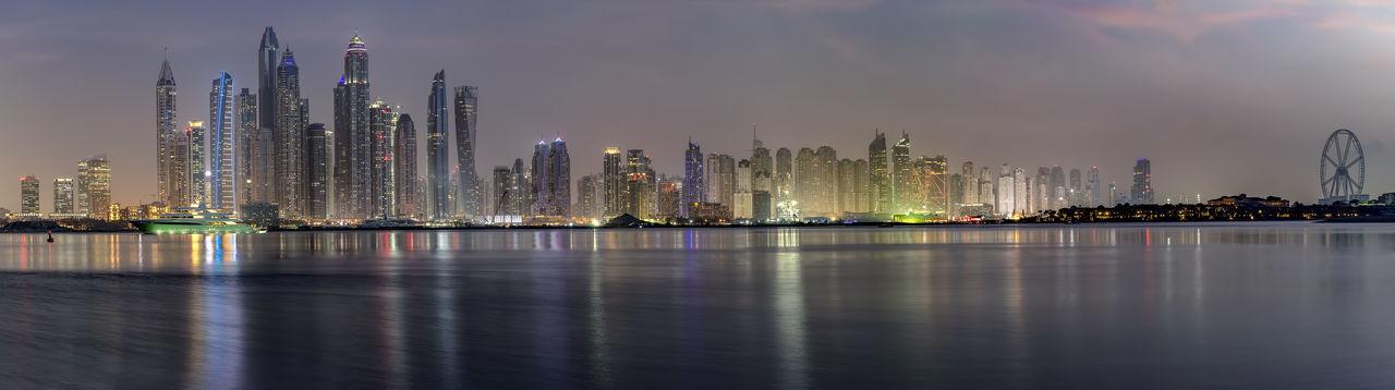 Illuminated modern buildings by city against sky