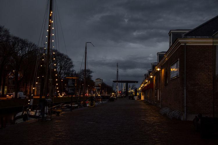 Illuminated street amidst buildings against sky at dusk