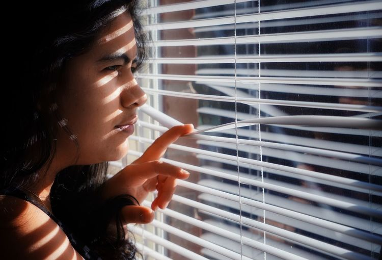 Close-up of woman looking though window blinds