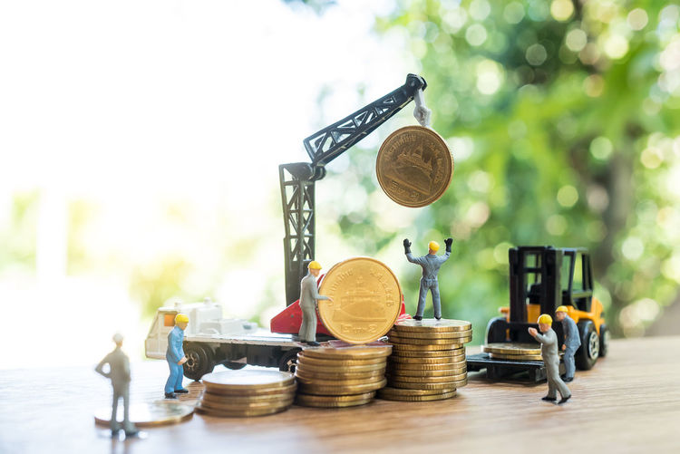 Close-up of figurines with toy crane and forklift with coins on table