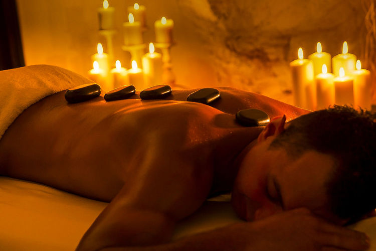 Shirtless man receiving hot stone therapy in spa