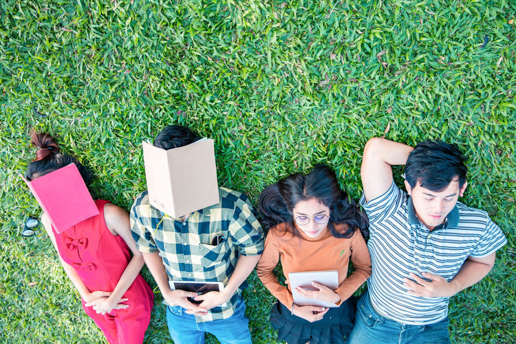 High angle view of students with books lying in lawn