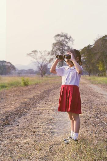 Full length of girl in school uniform looking through binoculars while standing at field