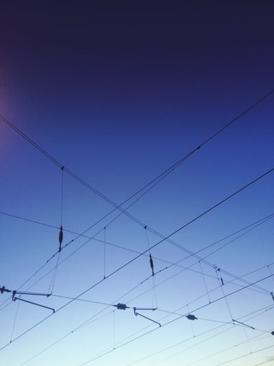 Low angle view of cable intersections against clear blue sky at dusk