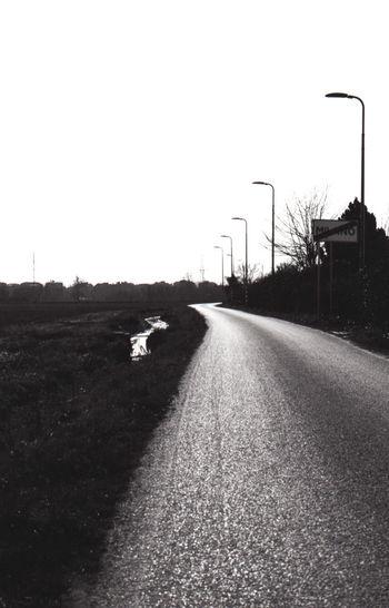 Street amidst field against clear sky