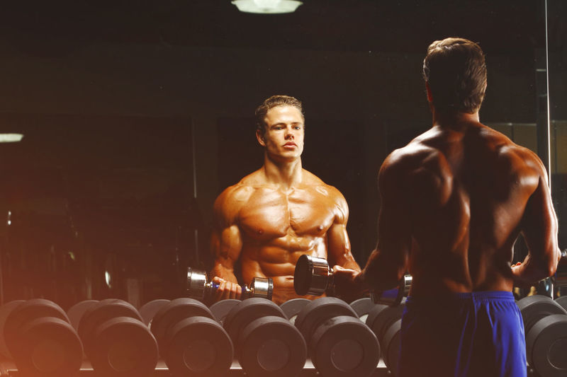 Rear view of shirtless man lifting dumbbells while looking in mirror