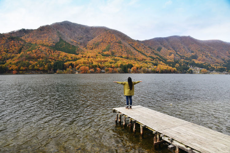 Rear view of woman standing on pier in lake against mountains