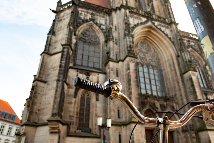 Low angle view of bicycle handlebar against historic building