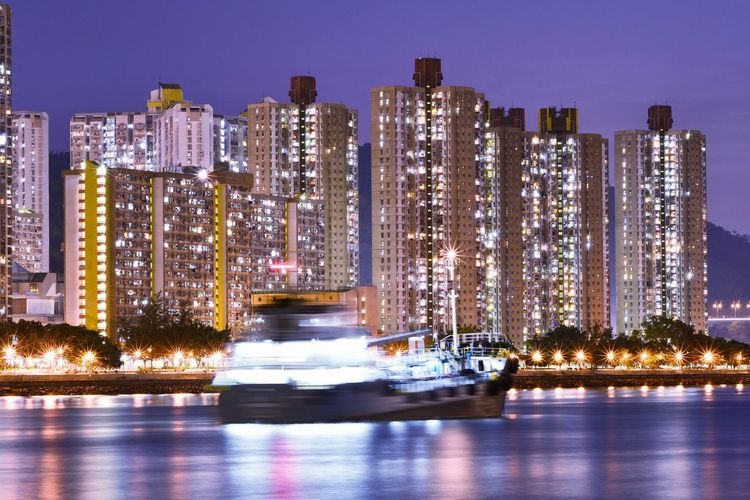 Blurred motion of boat sailing in river against illuminated buildings at night