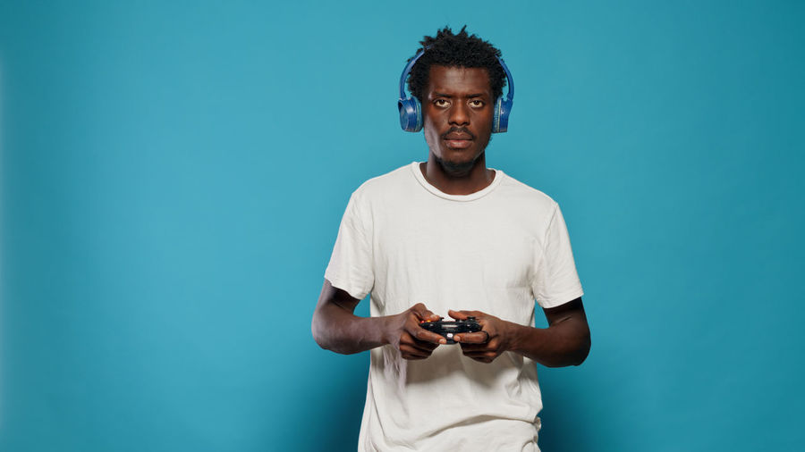Man holding camera while standing against blue background