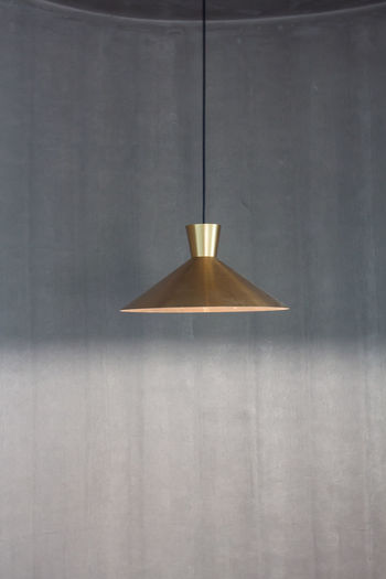 Close-up of electric lamp hanging on wall at home