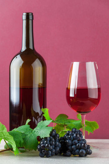 Red wine bottle and wineglass with ripe grapes on marble and pink background Alcohol Barrel Bottle Cellar Composition Cork - Stopper Drink Drinking Glass Food And Drink Fruit Grape Green Color Group Of Objects Leaf Liquid No People Red Red Wine Vine - Plant Wine Wine Bottle Wine Cask Wine Cellar Wine Cork Wineglass