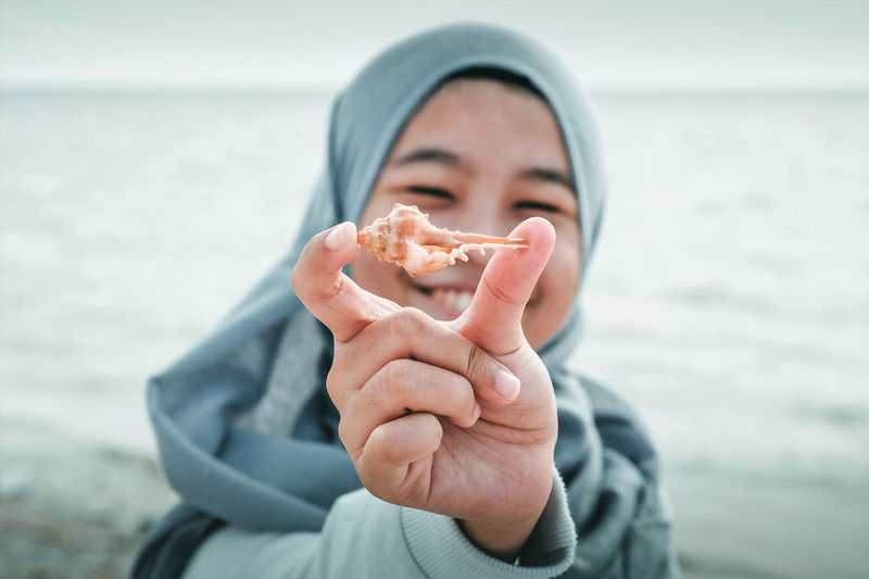 Woman In Hijab One Person Holding Sea Water Beach Front View Portrait Focus On Foreground Leisure Activity Headshot Close-up Nature Hand Outdoors Obscured Face Seashells Holiday Travel International Women's Day 2019