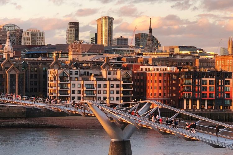 Bridge Over River Against Buildings In City At Sunset